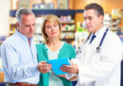 senior couple at pharmacy with doctor