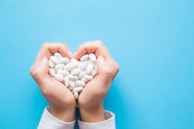 woman hands created a heart shape with medicines