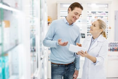 pharmacist using tablet while speaking with man