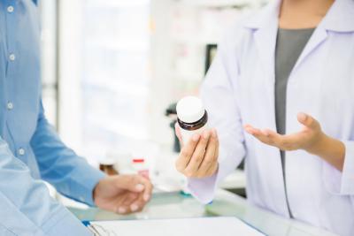 female pharmacist holding medicine bottle giving advice to customer